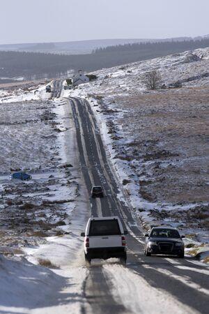 Winter lanscape across Dartmoor. Trafffic flow along the B3212 road close to Postbridge in the Dartmoor National Park in Devon England UK