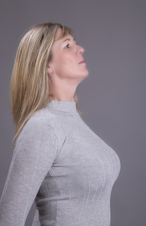 Portrait of a busty middle aged attractive woman wearing a grey top