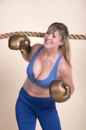 agachado: La mujer del boxeador con guantes de oro y un sujetador deportivo pasando por debajo de una cuerda Foto de archivo