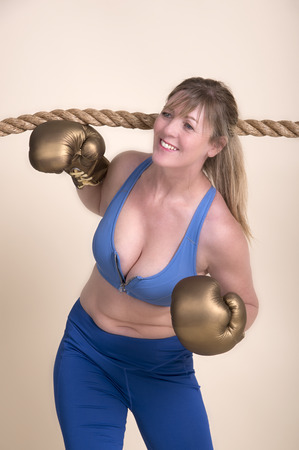 Woman boxer wearing golden gloves and a sports bra ducking under a rope