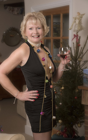 Elderly female party hostess with a glsss of wine