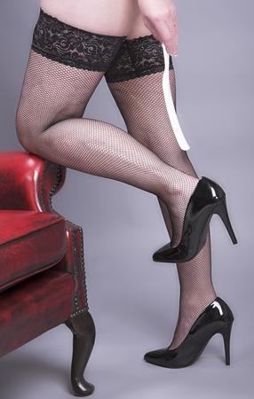 Beine in Netzstrümpfen und Hand mit einem Schuhanzieher
