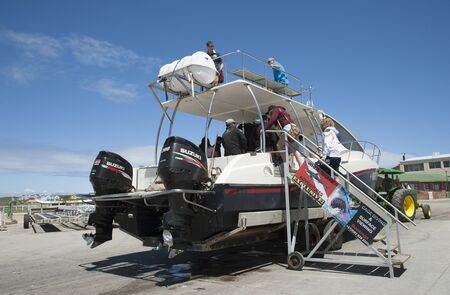 Great White shark dive boat at Kleinbaai Harbour in Gansbaai in the Western Cape South Africa. Dive boat customers board the boat on the quayside