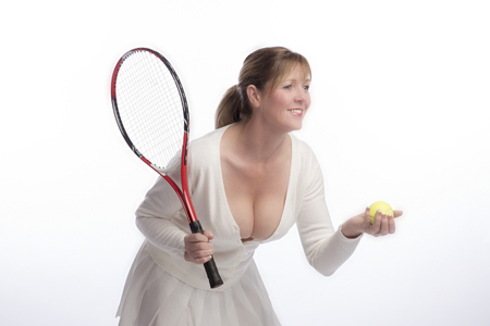 Middle aged female tennis player holding a raquet and yellow ball