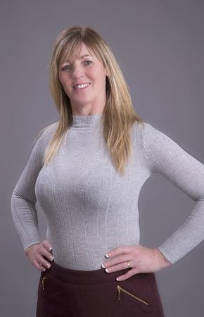 Aantrekkelijke midden oude rondborstige vrouw met de handen op de taille dragen van een strakke grijze trui
