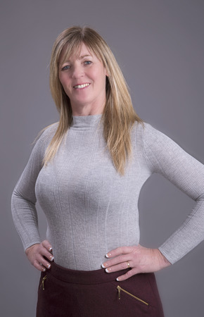 Attractive middle aged busty woman with hands on waist wearing a tight grey jumper