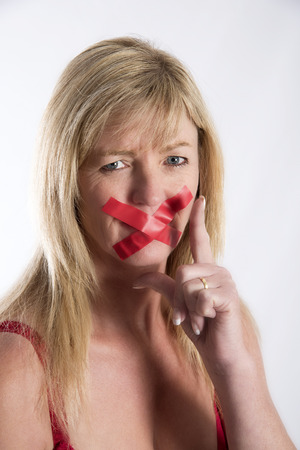 silenced: Woman with red tape strtched across her mouth Stock Photo