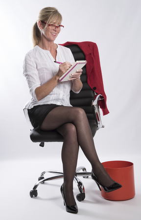 Female office worker with a pencil and notebook sitting in  a chair