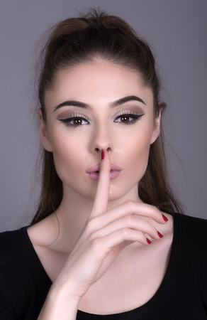 subdue: Portrait of a young woman holding finger to her lips