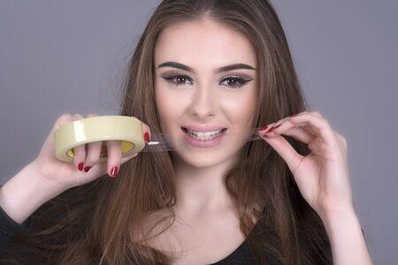attach         â     â       ©: Mujer rasgando una longitud de cinta adhesiva de un rollo con los dientes