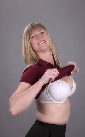 Woman pulling a tight fitting shirt over her bra
