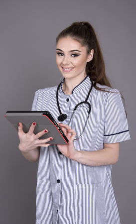 a lady doctor: Nurse in uniform with a stethoscope and electronic tablet