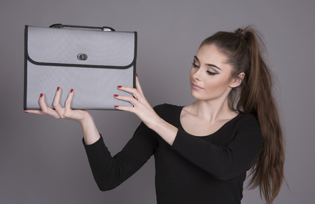 notecase: Woman carrying a plastic briefcase at shoulder height