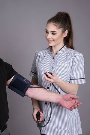 cuff: Nurse using a blood pressure monitor on a patient Stock Photo