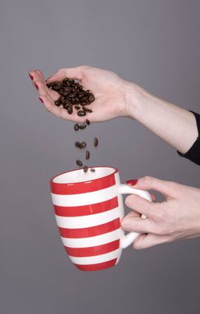 long bean: Young womans hand pouring fresh coffee beans into a red and white mug