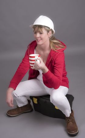 Woman worker wearing a hard hat and holding a mug