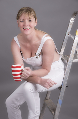 Worker wearing dungarees taking a tea break at her place of work Stock Photo