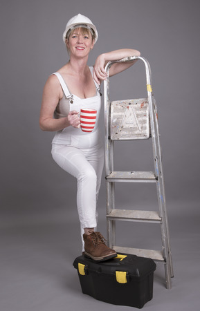onsite: Worker wearing dungarees taking a tea break at her place of work Stock Photo