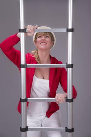 Woman climbing an aluminium telescopic ladder