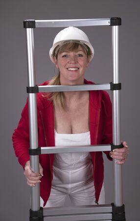 rungs: Woman climbing an aluminium telescopic ladder