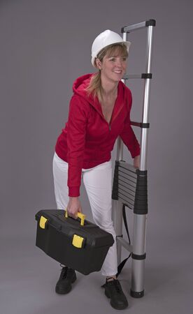 rungs: Female worker wearing a hard hat and holding a telescopic ladder