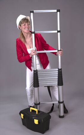 Female worker wearing a hard hat and holding a telescopic ladder