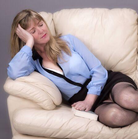 slumbering: Woman sleeping on a cream leather sofa