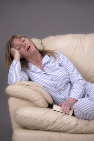 Woman wearing blue and white striped pyjamas sleeping on a cream leather settee