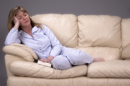 catnap: Woman wearing blue and white striped pyjamas sleeping on a cream leather settee