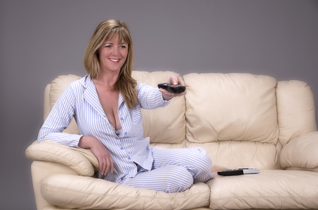 Woman wearing pyjamas and holding a tv controller seated on a settee