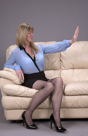 Woman using body language and palm of hand in a gesture of keep away