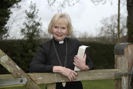 庭の門に寄りかかって年配の女性牧師