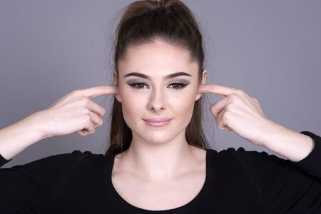 Young attractive woman with fingers in her ears