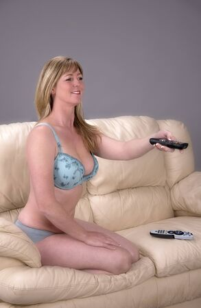 Woman in underwear holding a television remote controller
