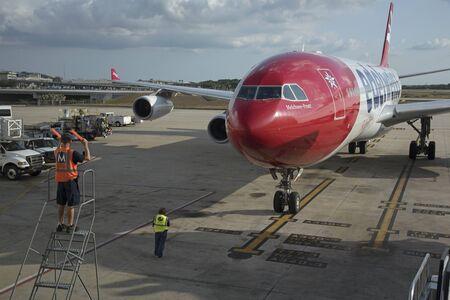 El comandante de la aeronave utiliza palos de señalización para guiar un avión de pasajeros grande a una posición exacta en la plataforma del aeropuerto de Tampa USA. Mayo de 2017 Foto de archivo - 77866896