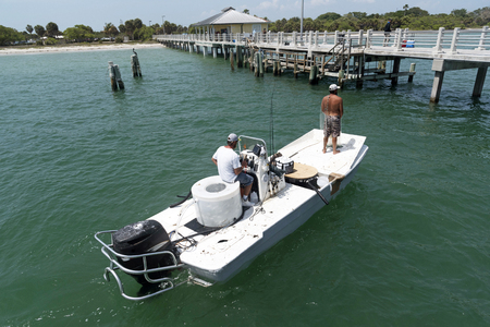 Fishing for bait using a cast net from a small boat on the Gulf of Mexico Florida USA