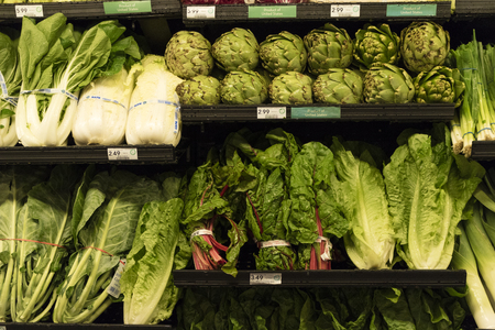 Vegetables and salad produce on a supermarket shelf Editorial
