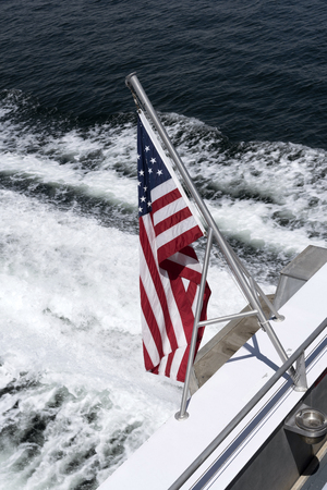 The American Stars and Stripes flag mounted on the stern of a bot with the wash as a backdrop,