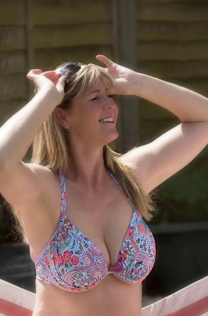 Woman wearing a bikini top annd holding sun glasses in her hair