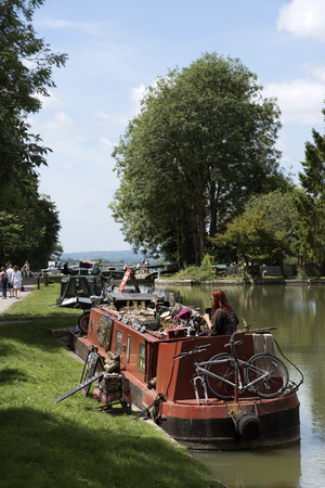 Canalboat on the Kennet & Avon Canal selling a selection of brass craftwork. Devizes Wiltshire England UK Editorial