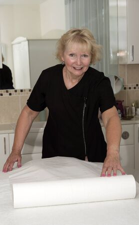 hygenic: Masseuse preparing the client bed with a paper roll