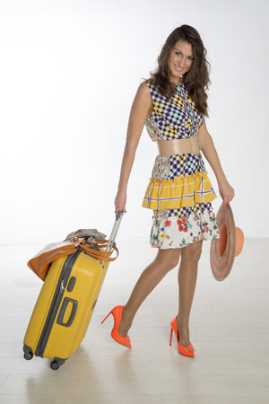 Woman holidaymaker in colorful clothing and a yellow suitcase