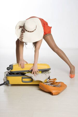 Holidaymaker packing a suitcase, summer clothing and a large hat