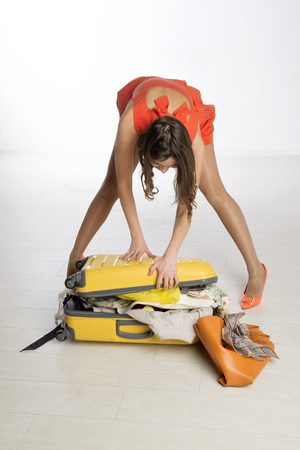 Holidaymaker trying to close her suitcase