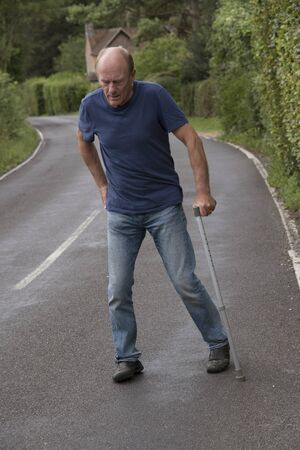 Elderly disabled man with back pain using a walking stick