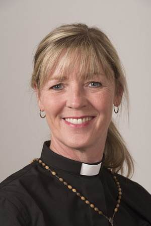 Portrai of a woman priest with blond hair and a big smile
