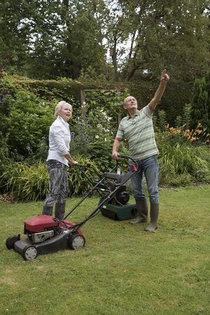 oap: Man and woman with lawn mowers working in a country garden. Man pointing. Stock Photo