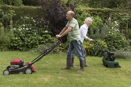 oap: Man and woman with lawn mowers working in a country garden