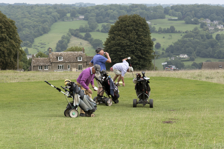 oap: Three elderly golfers playing golf in the south Cotswolds region of England UK. August 2017