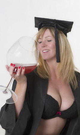 Portrait of a female mature student wearing a black gown holding a glass of wine and revealing her cleavage
